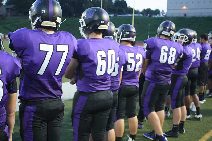 Varsity football players stand by, ready for action on the sidelines.