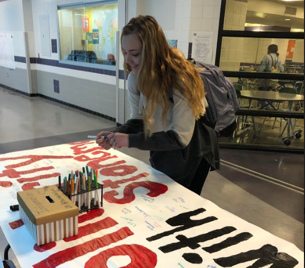 Junior+Hailey+Guzzi+signs+poster+for+Parkland+students.