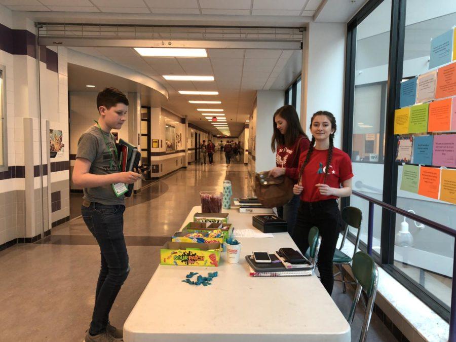 Sophomores Feride Radzhapova Renee Firek selling candy to freshman Aidan Greenaway.