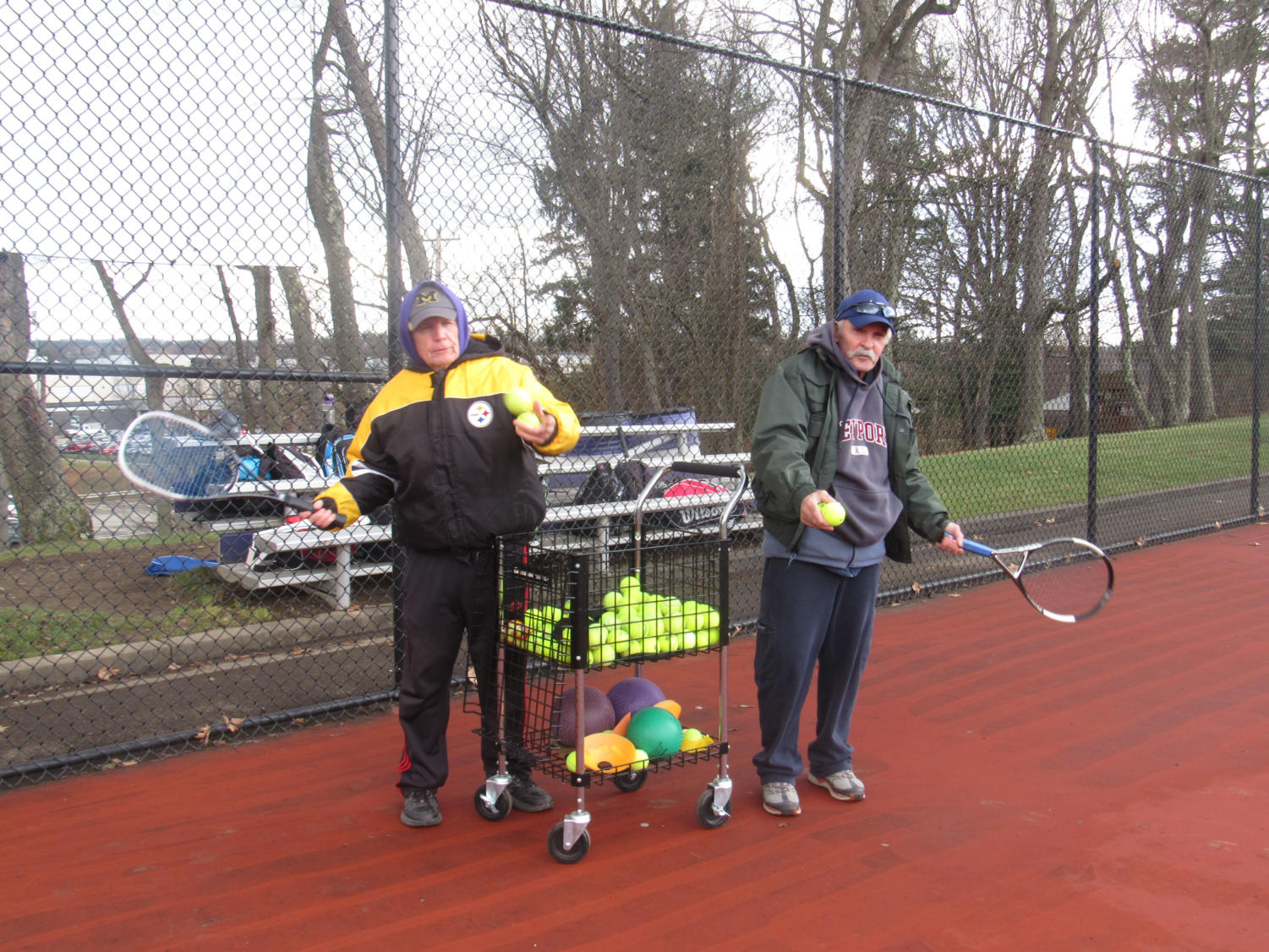 New tennis coaches Tom Kirk (left) and Dave Shenefelt (right) prepare to feed tennis balls to players in warm-ups. The coaches hope to lead their team to playoffs this season.