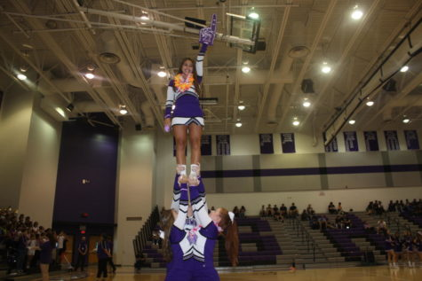 Cheerleader Alaina Woderak practices stunts at the fall sports pep rally.