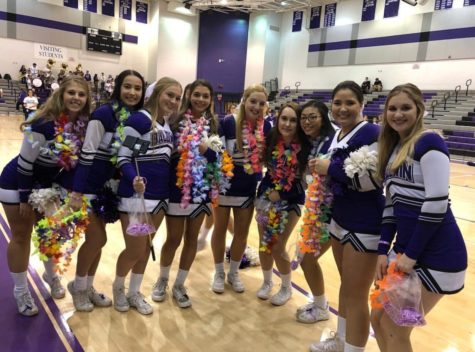 The varsity cheerleaders help pep up students for the football game.