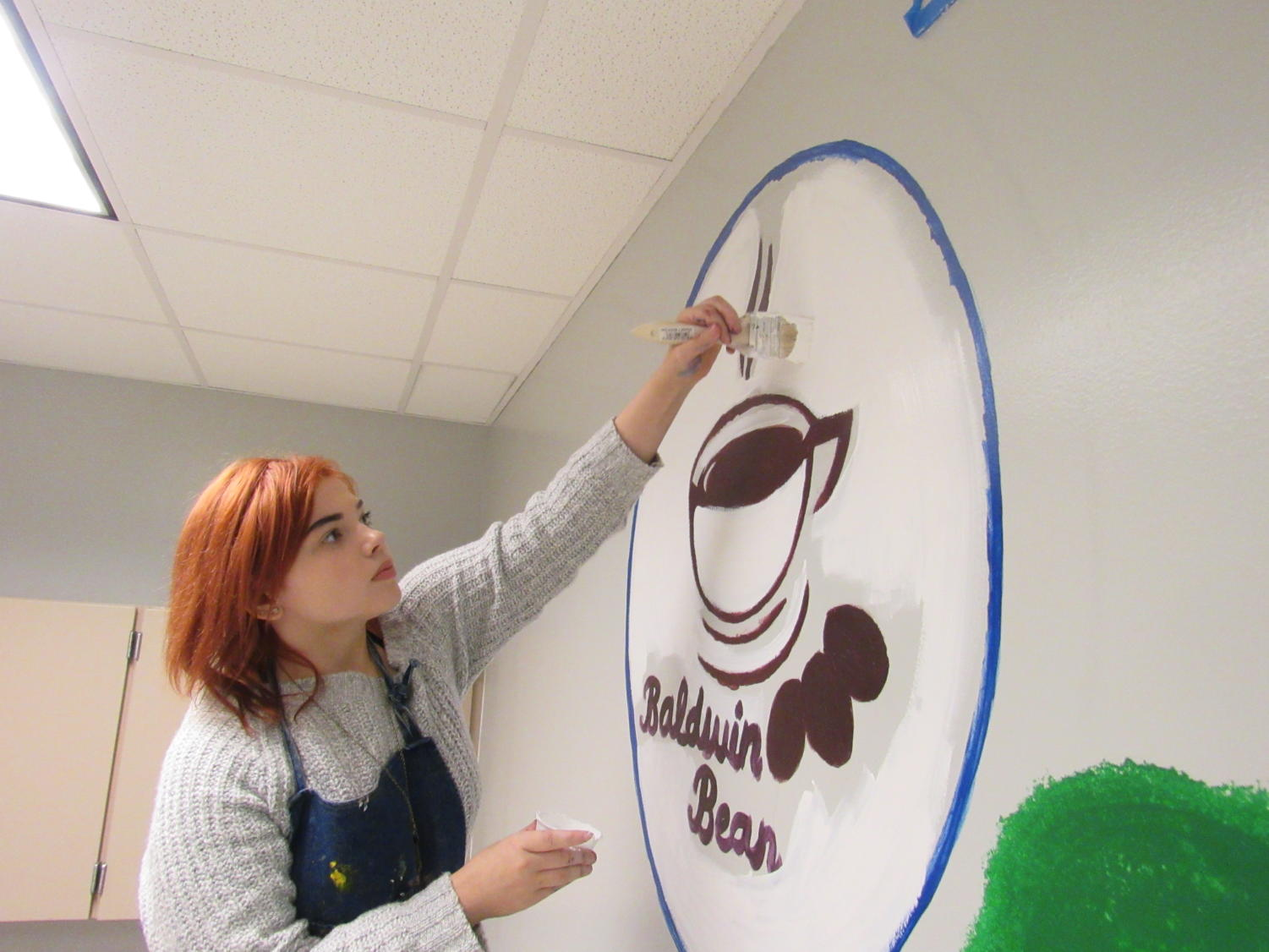 Preparing the Bean: Senior Alexis Primrose paints the inside of the Baldwin Bean. The coffee shop will be open first and second periods.