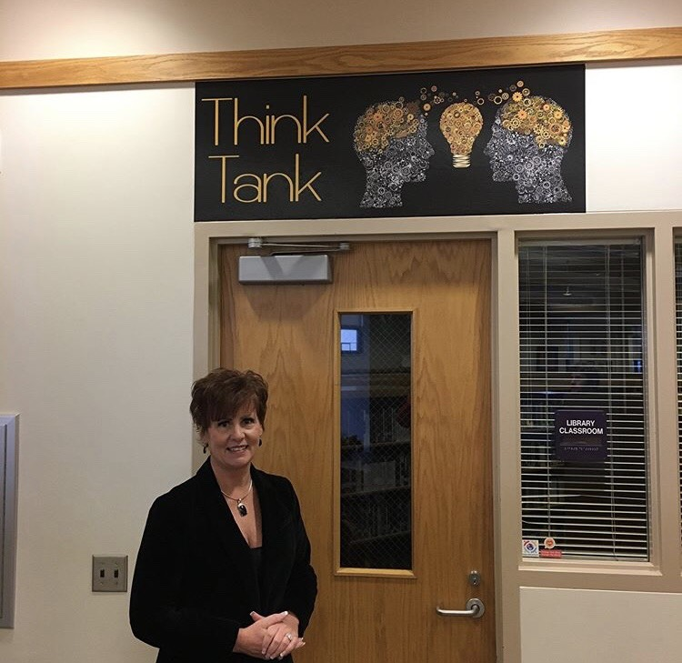 Library Media Specialist Brigetta Del Re stands by the new sign of the Think Tank, a group collaboration room in the library.