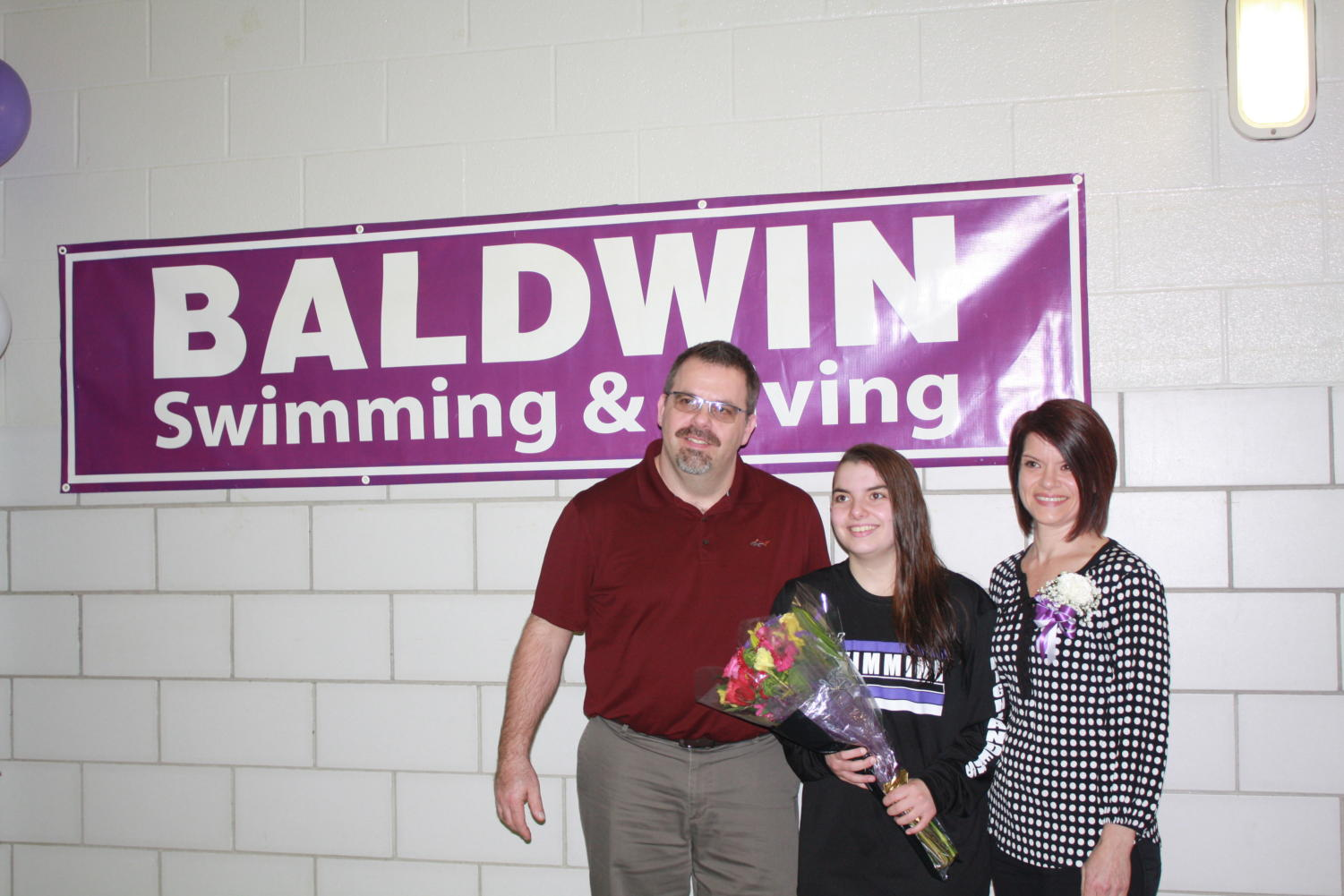 Senior+Camryn+Beveridge%2C+four+year+swimmer%2C++posing+with+parents.+
