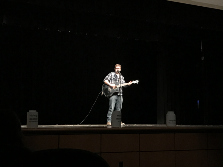 Mitch Holmes sings and plays guitar during the talent show.
