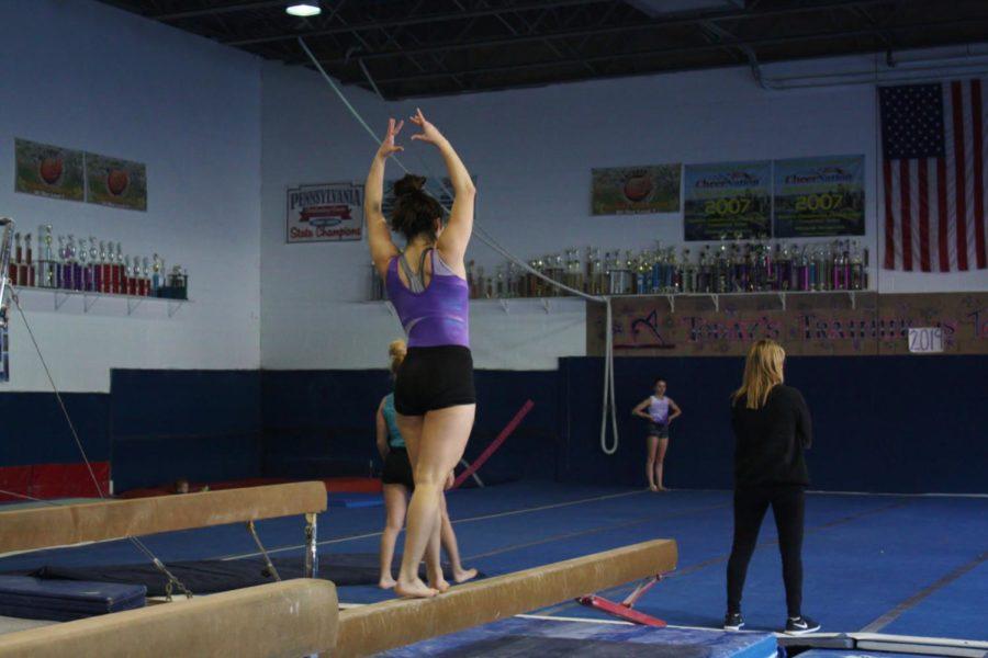 Gymnasts practice balancing on the beam.