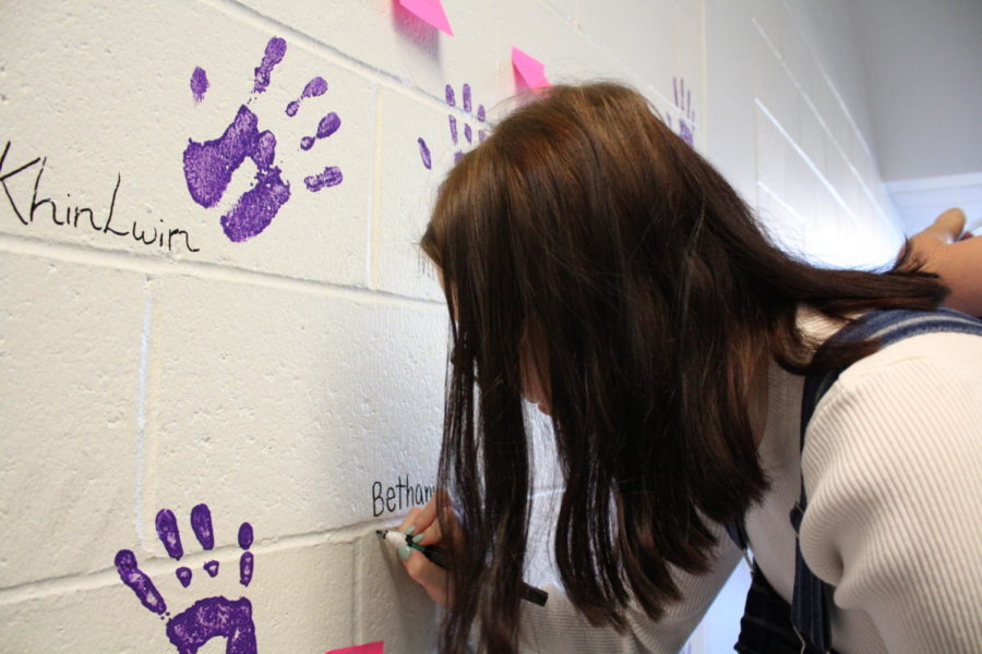 Bethani Rechtorik writes her name to prepare for her hand print.
