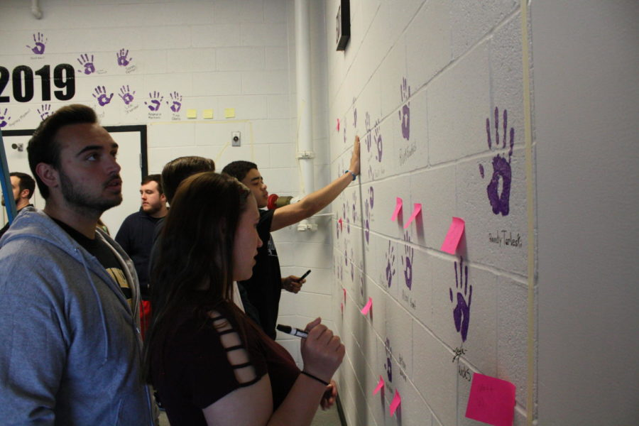 Senior Addy Tagg chooses where to place her hand print.