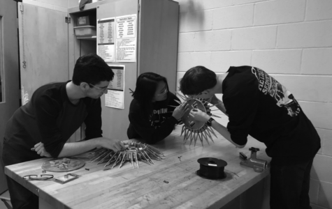 Building the bot:  Seniors Joshua Luxemburger (left), Yee  Khine (middle), and Billy Andrews work on building a robot for their upcoming competition. This year, the club is working on a new design for their robot.