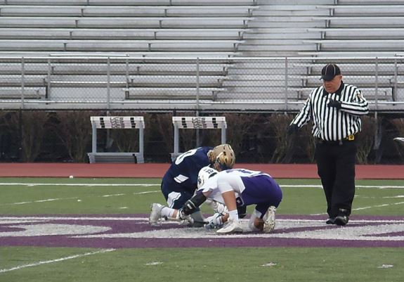 Two players scramble for the ball. Boys lacrosse took a tough loss Friday.