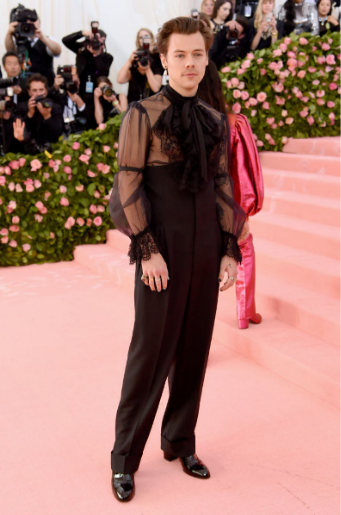 Harry+Styles+wore+an+all-black+Gucci+outfit+that+included+many+feminine+touches%2C+like+a+pearl+earring+and+a+sheer+lace+top.