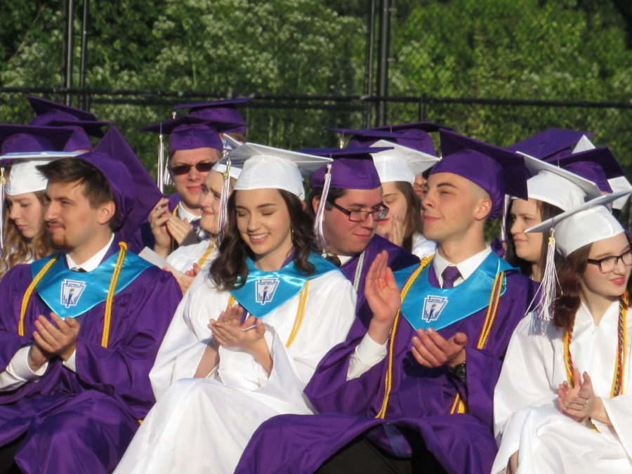 Students cheer on their fellow classmates as they receive their diplomas.