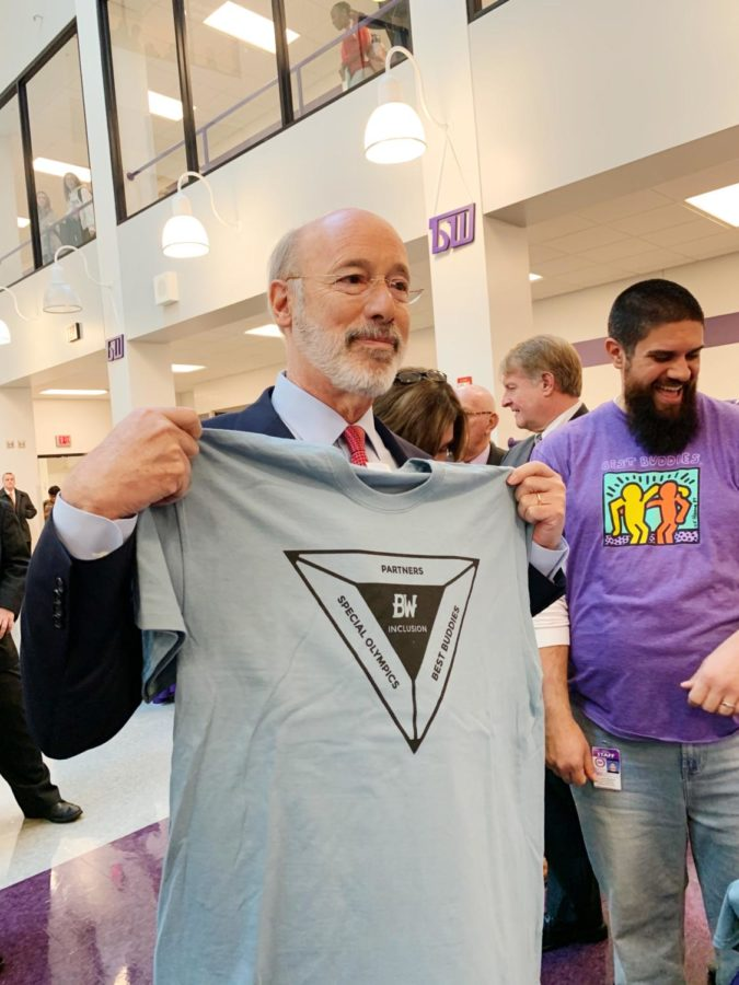 Governor Tom Wolf holds up a Special Olympics shirt. The governor visited the high school on Friday.