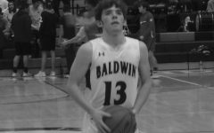 Senior Andy Degenhardt focuses on scoring points at a basketball game before taking a shot. He has played the sport since third grade.