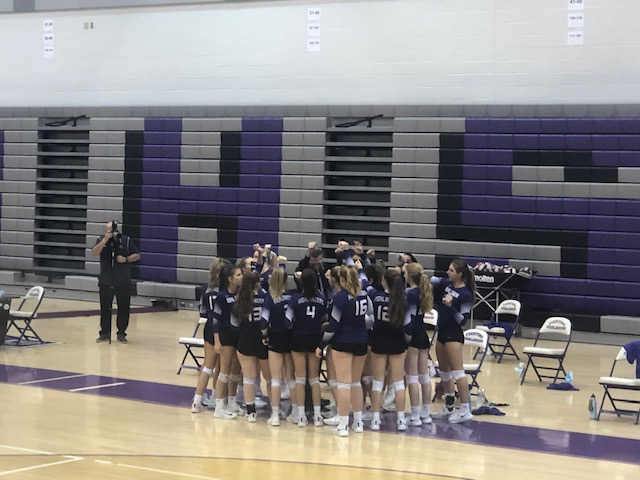 The Baldwin girls volleyball coach talks to the team during a break in the game.