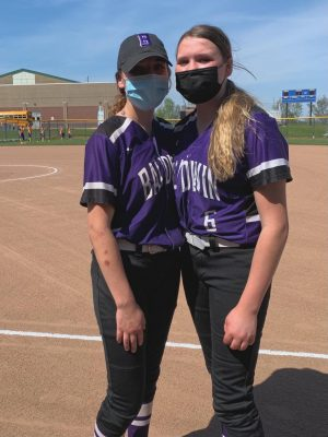 Picture of Grace and Anna Schumacher standing together before their softball game.